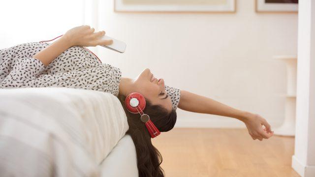 Eine Frau mit roten Kopfhörern liegt auf dem Bett und hört etwas auf ihrem Handy.