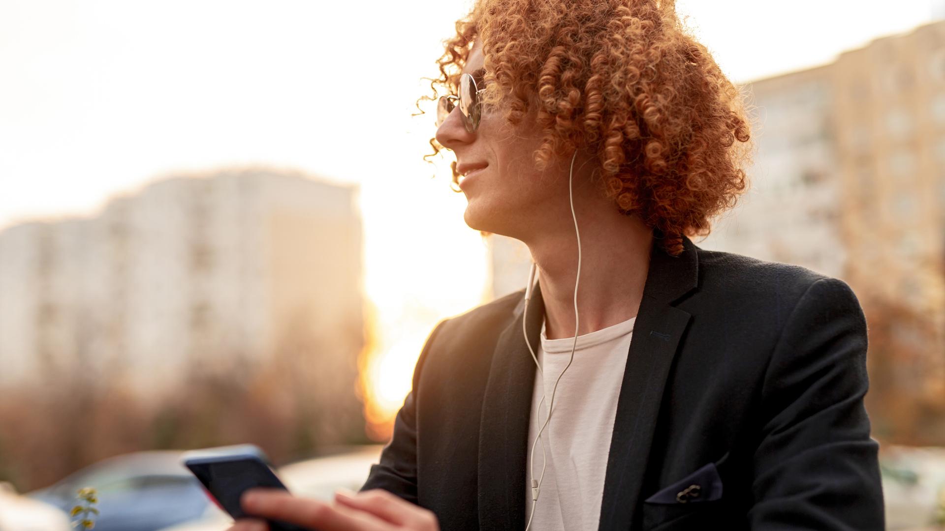 Ein Mann mit Sonnenbrille ist draußen unterwegs und hört per Kopfhörer etwas auf seinem Handy an.