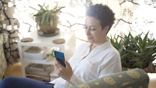 Eine Frau sitzt mit ihrem Smartphone in einem Sessel, umgeben von Pflanzen