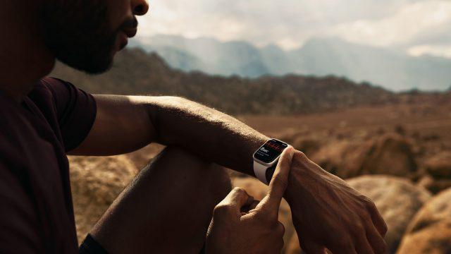 Mann in Wüste beim Sport guckt auf Apple Watch 7 am Handgelenk