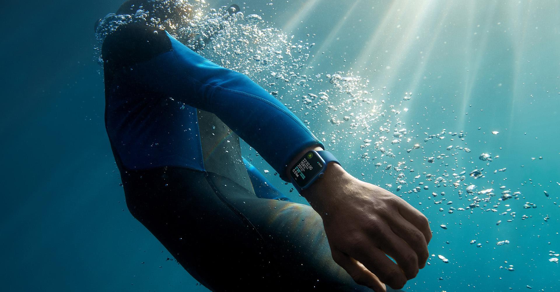 Person mit Neoprenanzug trägt die Apple Watch 7 unter Wasser
