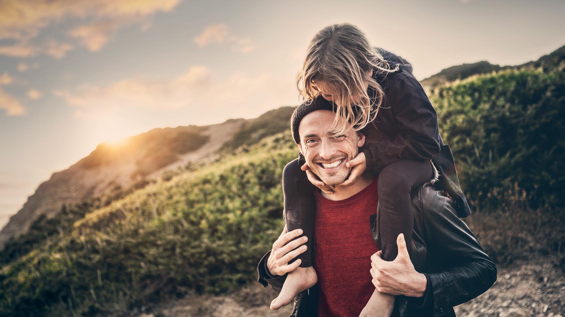 Ein Vater trägt seine Tochter auf den Schultern, sie stehen an einem Berg.