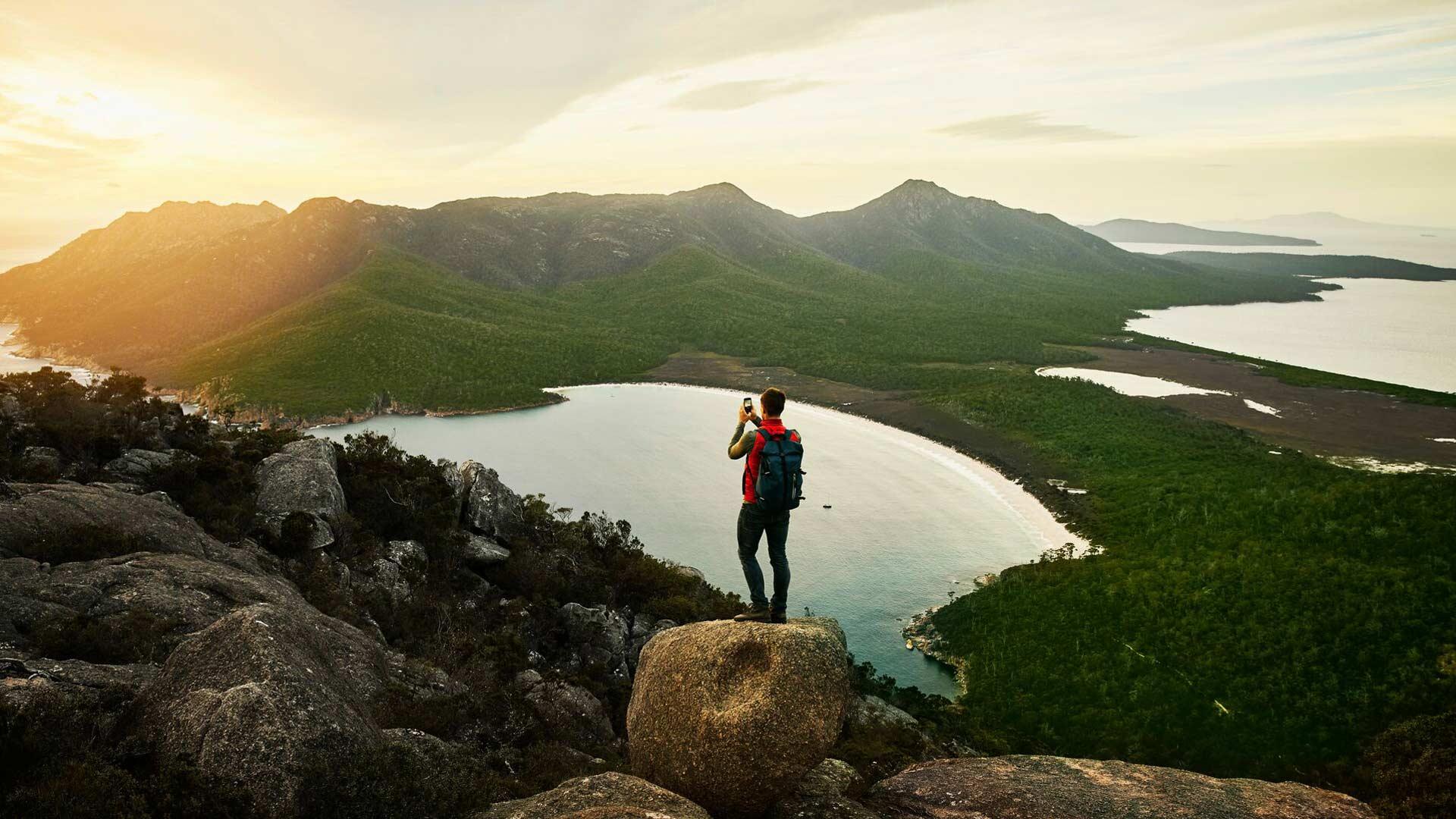 Ein Mann steh auf einem Berg und fotografiert den See im Tal mit seinem Smartphone.