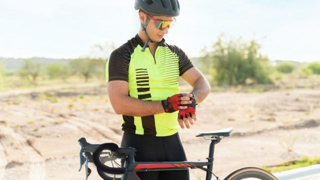 Fahrradfahrer schaut auf seine Smartwatch.