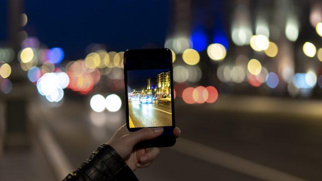 Frau macht mit dem Smartphone ein Foto bei Nacht