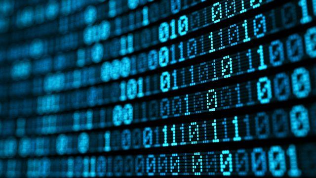 Ein Bildschirm zeigt binären Code in blauer Schrift an.