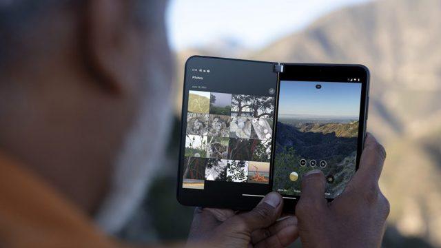 Mann hält Falt-Smartphone Surface Duo 2 vor Berglandschaft