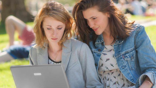 Zwei Frauen im Park gucken auf einen Laptop-Bildschirm