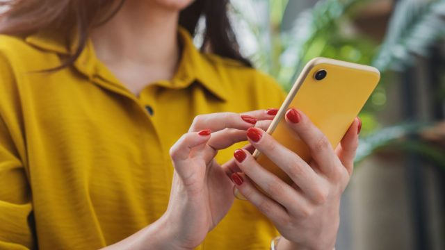 Frau chattet an ihrem Handy.