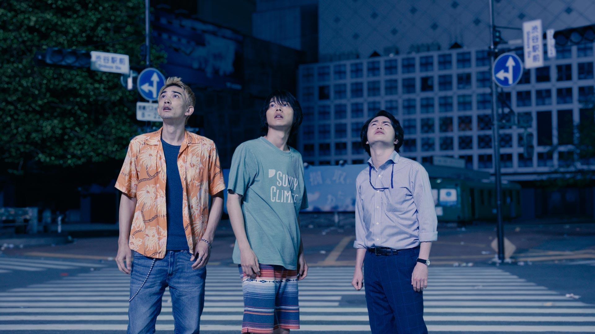 Drei Männer stehen auf einer Straße in Tokio und schauen in den Himmel