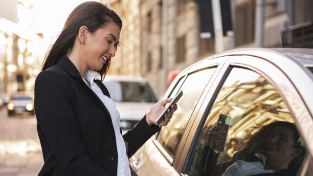 Frau öffnet Tür eines Autos, während sie ihr Smartphone in der Hand hält.