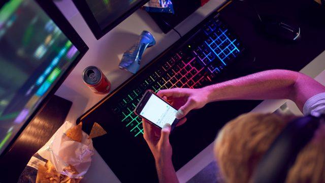 Gamer, der auf seinem Smartphone chattet.
