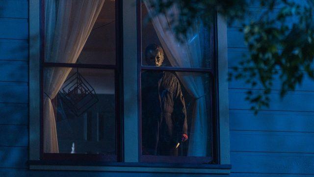 """Michael Myers steht in """"Halloween Kills"""" am Fenster eines Hauses."""