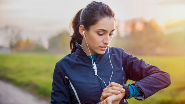 EIne Frau in Sportkleidung prüft draußen ihre Smartwatch.