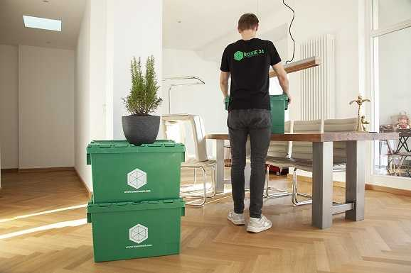 Two green moving boxes and a man transporting one