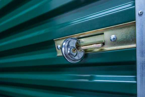 A green self storage door with an lock on it