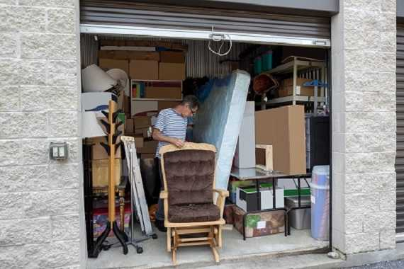 A man standing in his storage for furniture