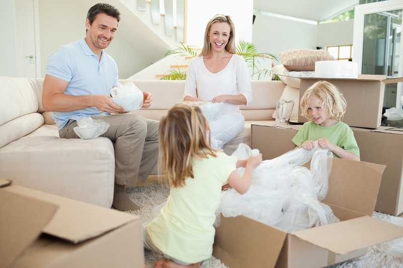 A family is packing up their home in cardboard boxes