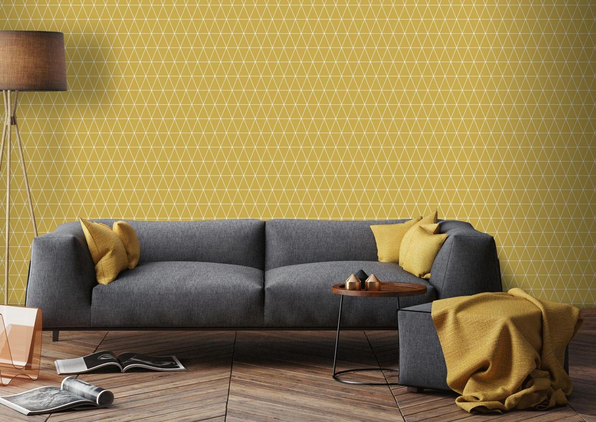 Vliesbehang met een geometrisch driehoek patroon in oker geel (dessin 100270) van Graham & Brown.
