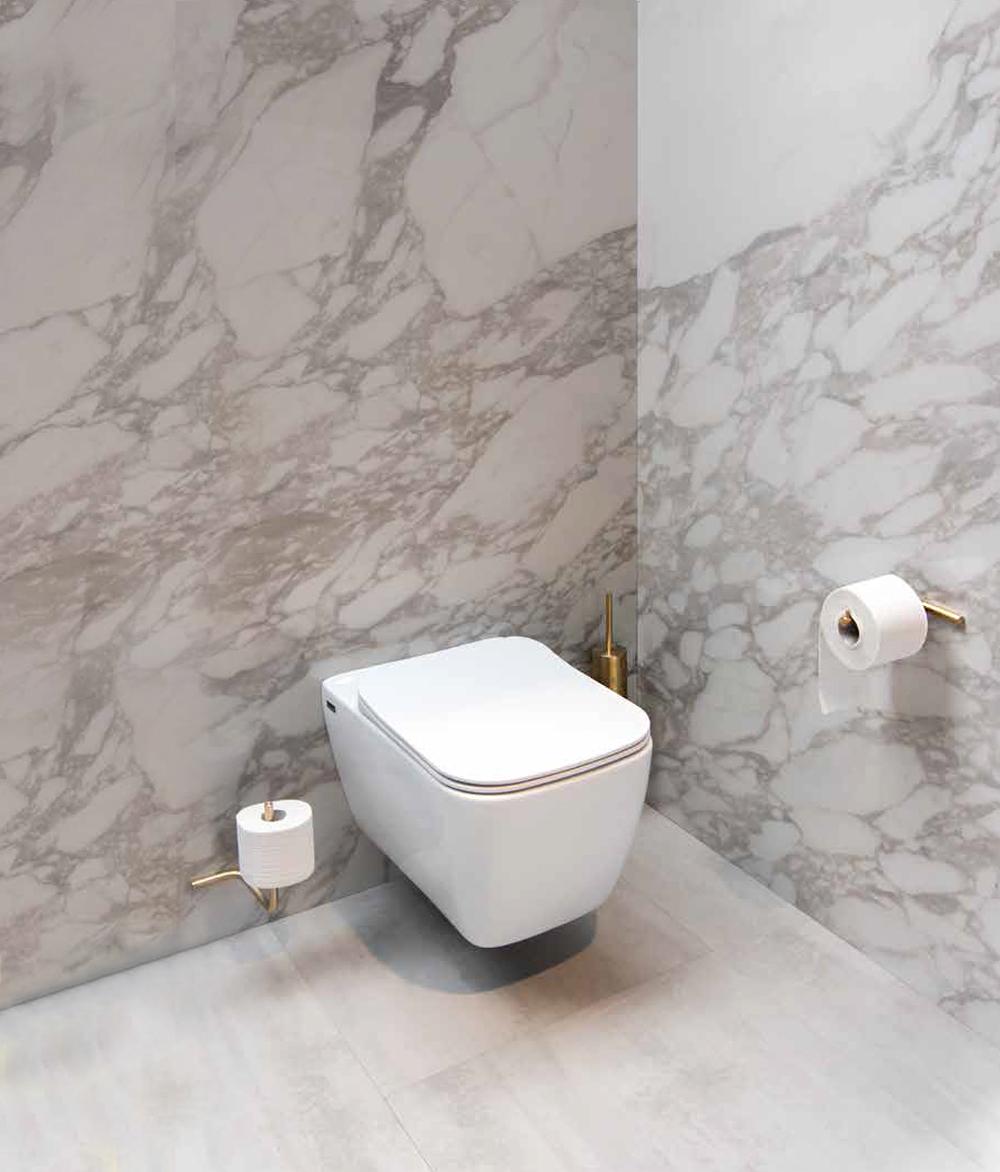 Een chique toilet met marmeren tegels en goudkleurige, moderne toiletaccessoires van Dekker.