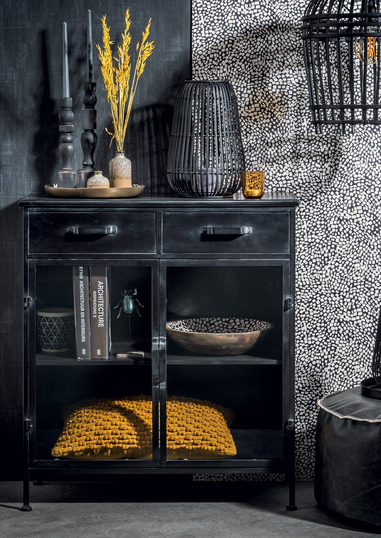 Zwarte wandkast met zwarte en okergele accessoires.