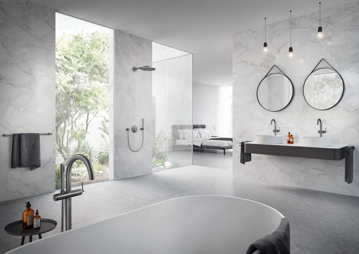 Geborstelde kranen in Hard Graphite (grafiet) staan mooi in een lichte badkamer met marmer.