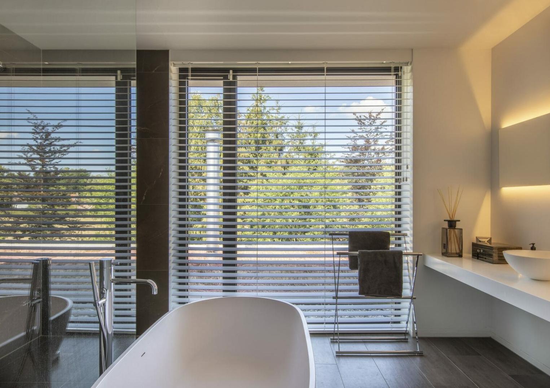 Brede houten jaloezieën in de badkamer.