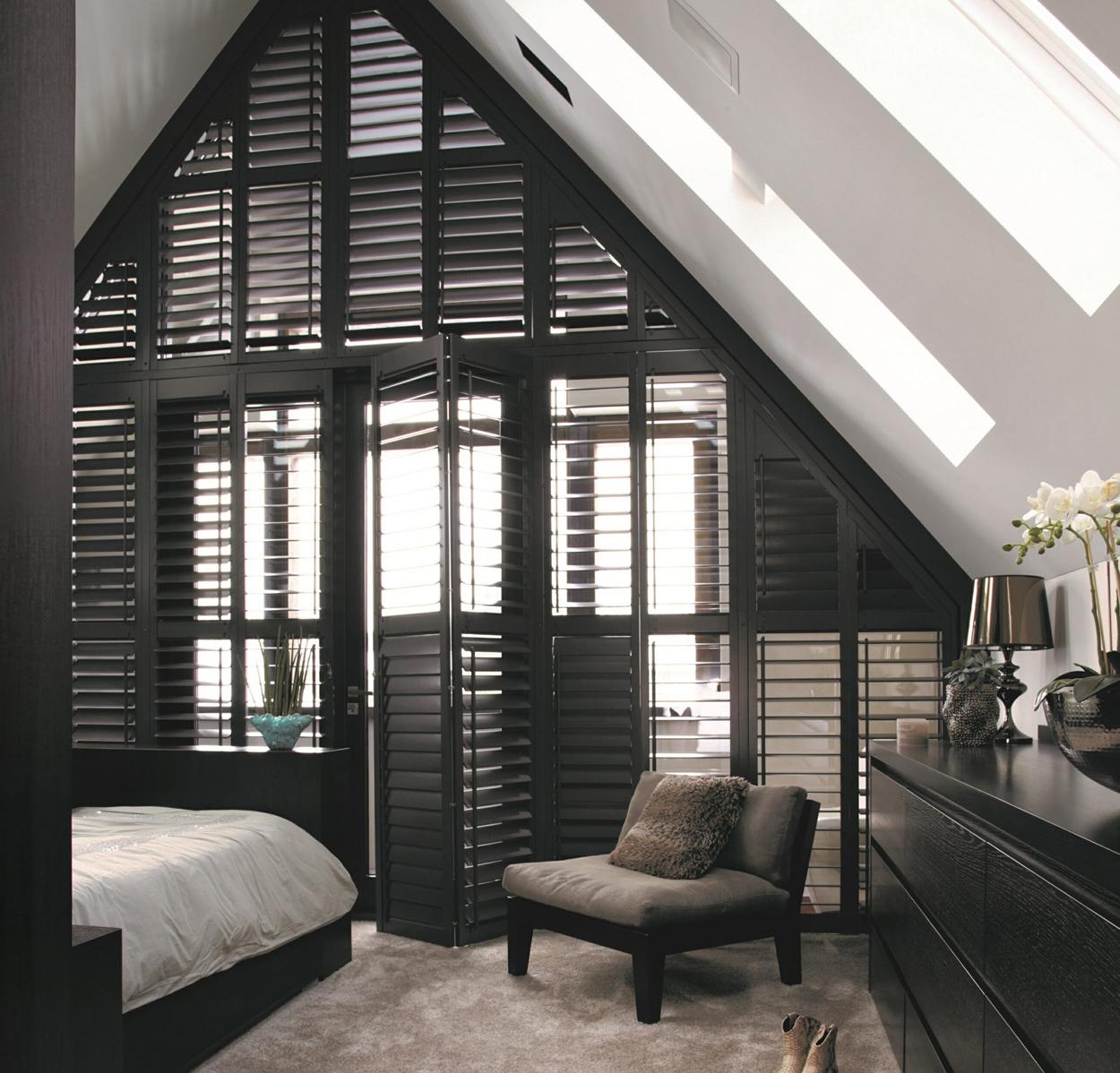 Stijlvolle, zwarte shutters in de slaapkamer als room divider.