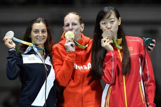 Rio de Janeiro, 2016. augusztus 6. A párbajtõrben olimpia bajnok Szász Emese (k) megcsókolja aranyérmét az eredményhirdetésen, mellette a második helyezett olasz Rossella Fiamingo (b) és a bronzérmes kínai Szun Ji-ven a Rio de Janeiró-i 3-as Karióka Arénában 2016. augusztus 6-án. Szász Emese a 2016-os riói nyári olimpia nõi párbajtõrversenye döntõjében 15-13-ra gyõzött az olasz Rossella Fiamingo ellen. MTI Fotó: Czeglédi Zsolt