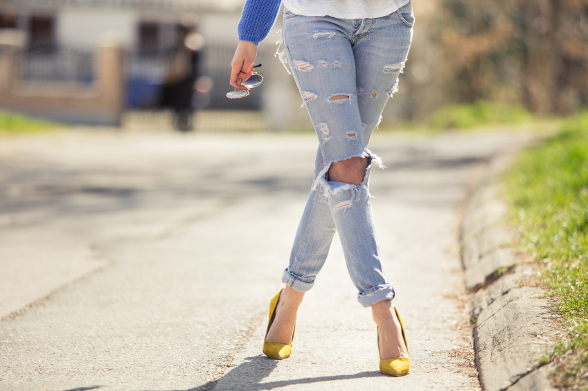 Woman legs in high heel yellow shoes on the road