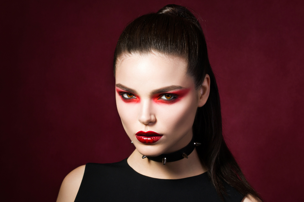 Young beautiful gothic woman with white skin and red lips