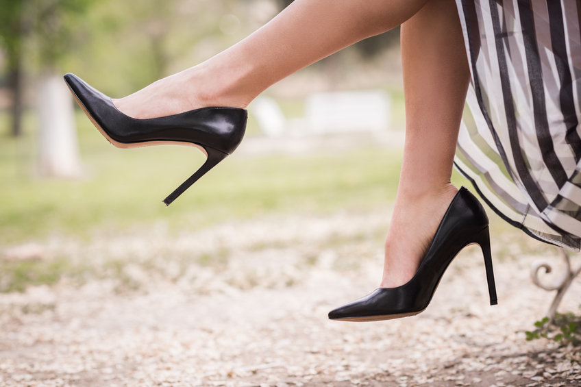 Black high heels on the feet of a young woman