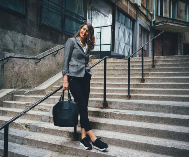donna business in posa su scala con sneakers nere