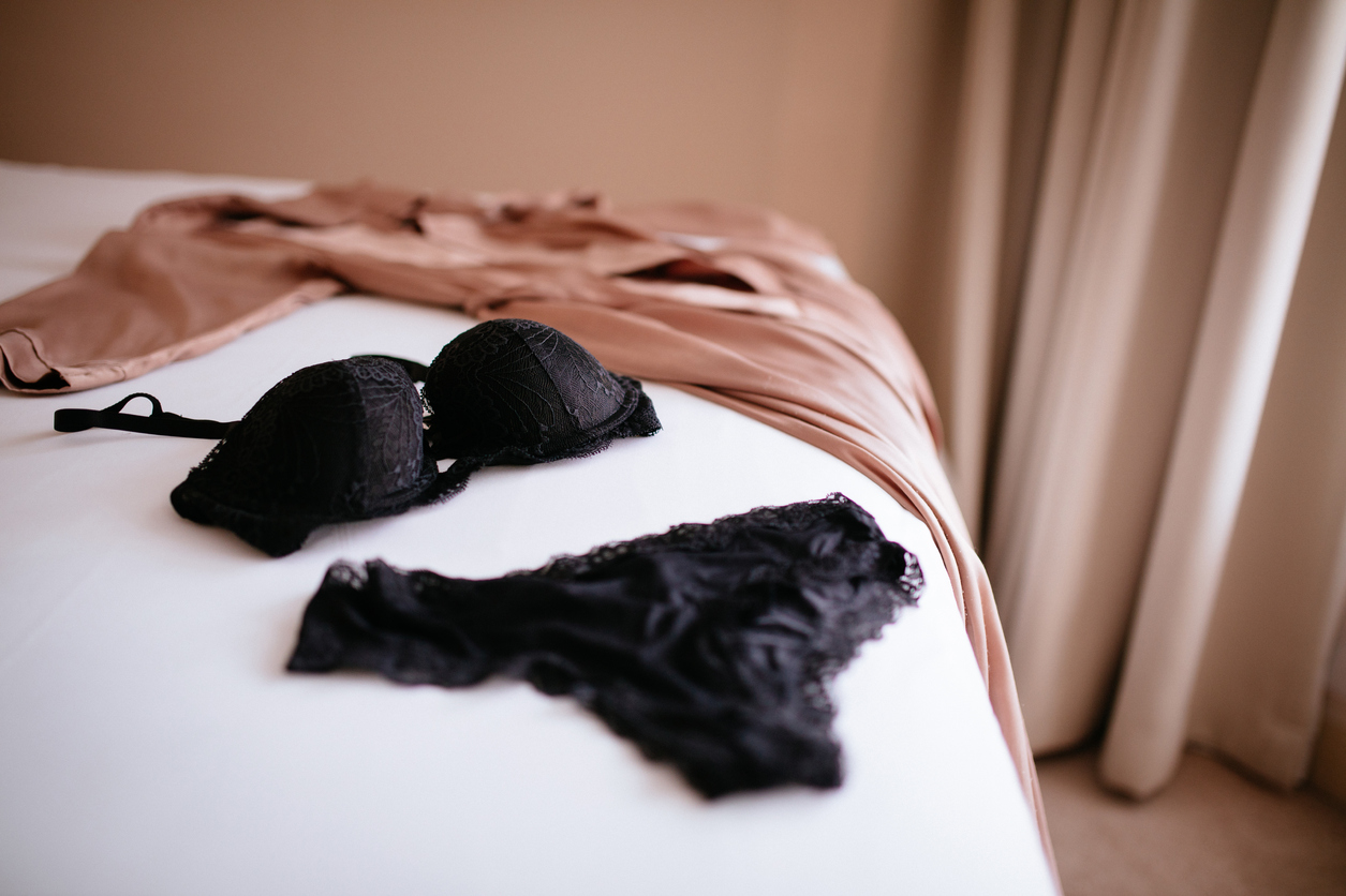 Black lace lingerie and silk robe placed in display on white sheeted bed