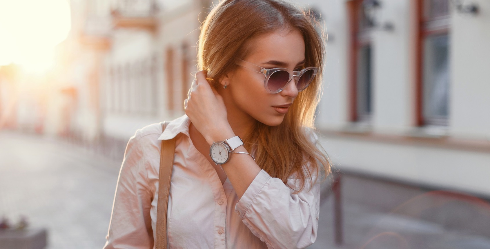 Beautiful girl in stylish sunglasses and with bag at sunset.
