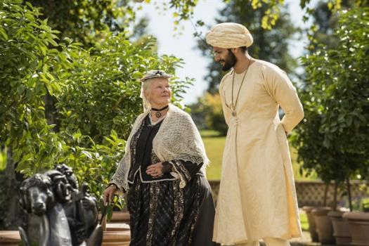 Victoria en Abdul wandelen in de tuinen.