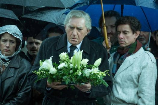 Albert legt bloemen neer bij het graf.