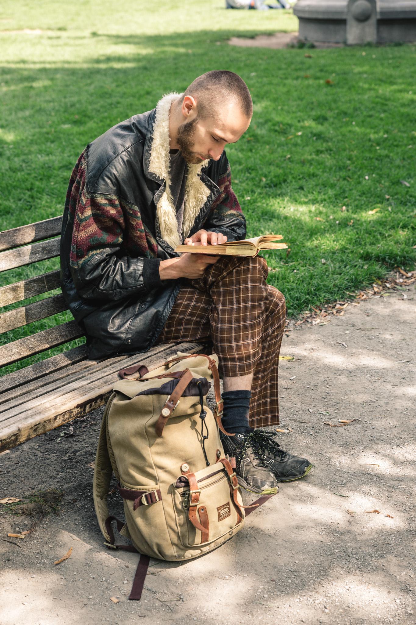 Lezende man in het park op een bankje