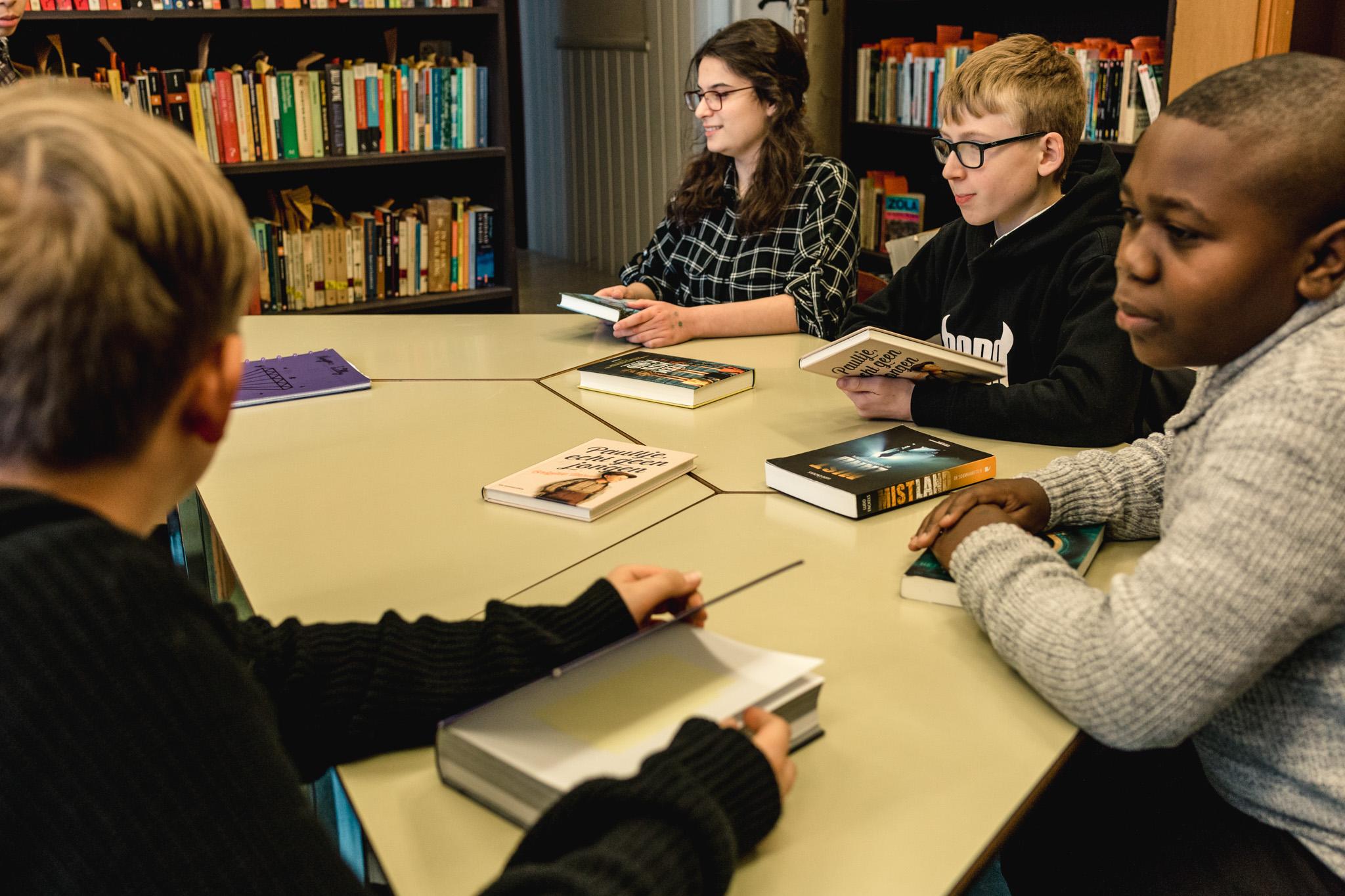 Leerlingen praten over boeken in de schoolbibliotheek