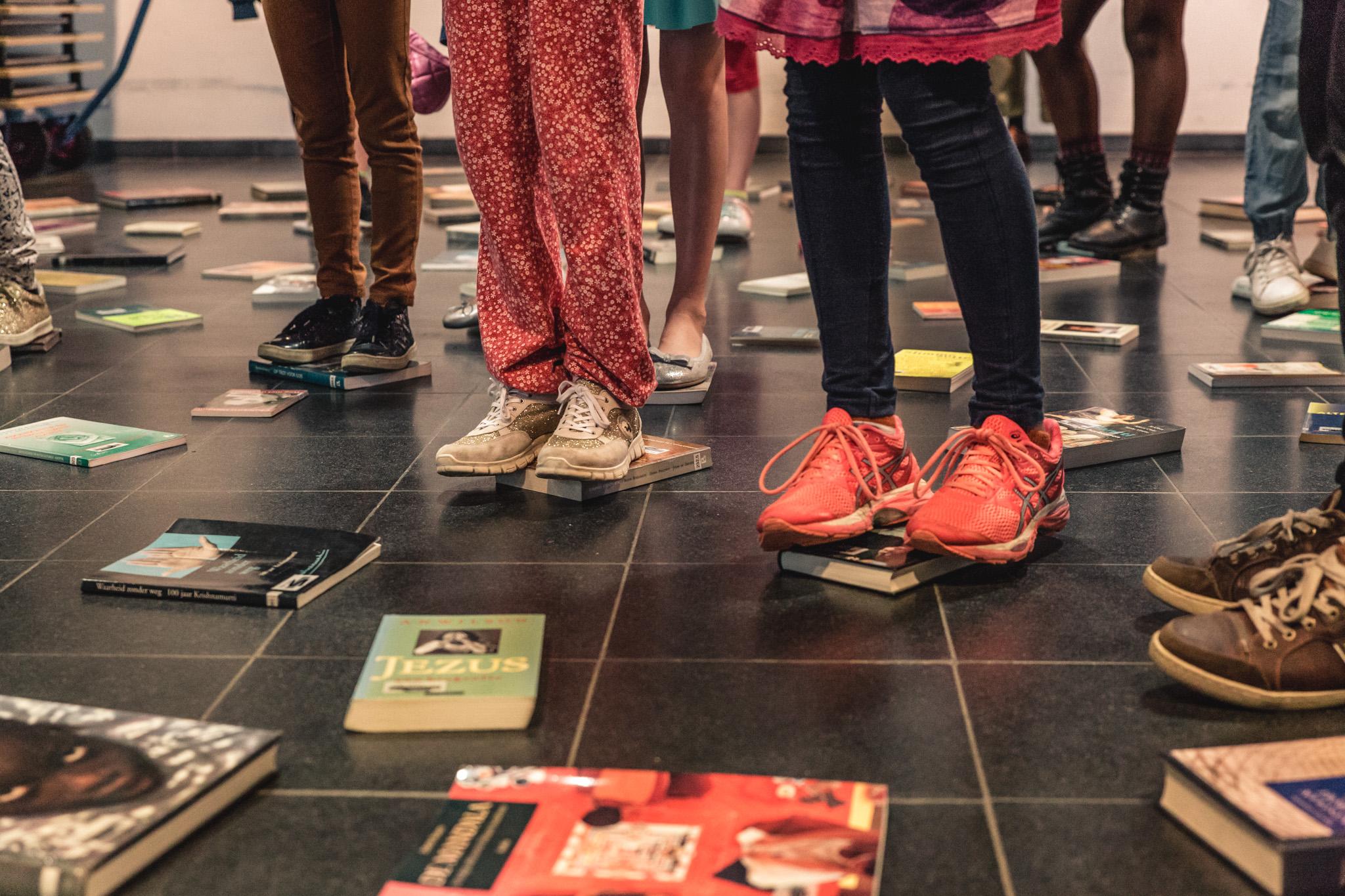 Tal van boeken liggen op de grond, kinderen kiezen hun favoriet door voorzichtig op het boek te gaan staan