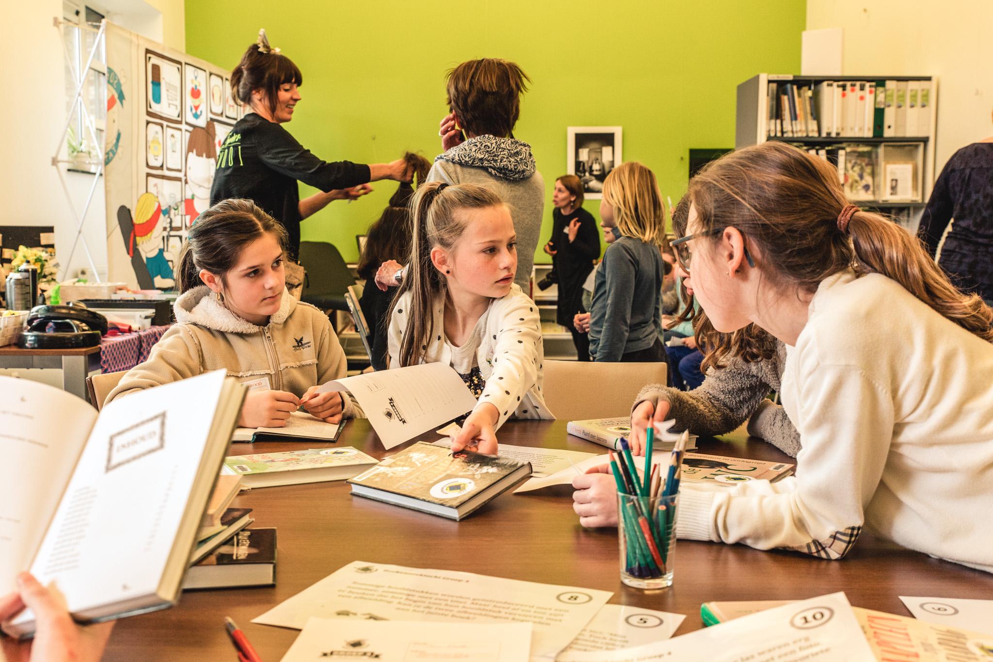 Kinderen werken rond boeken in de klas