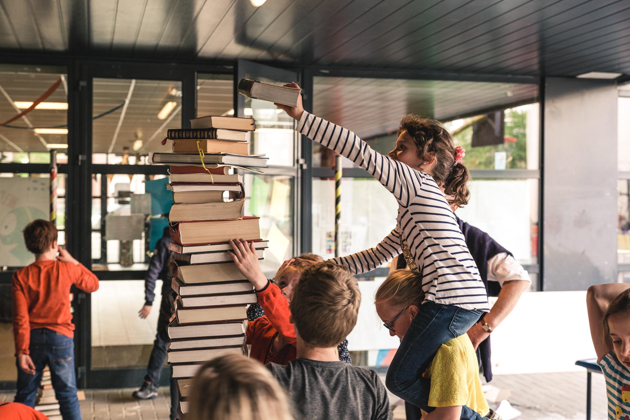 kinderen maken een toren van boeken