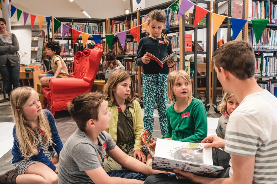 kinderen luisteren naar een jeugdauteur in de bib