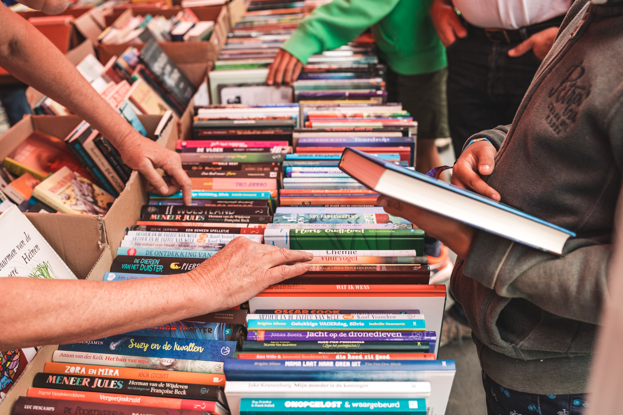 mensen snuisteren door boeken op een boekenmarkt