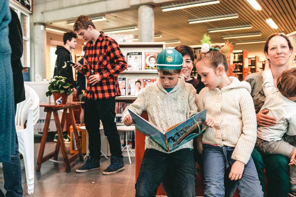 kinderen lezen samen in een prentenboek in de bibliotheek