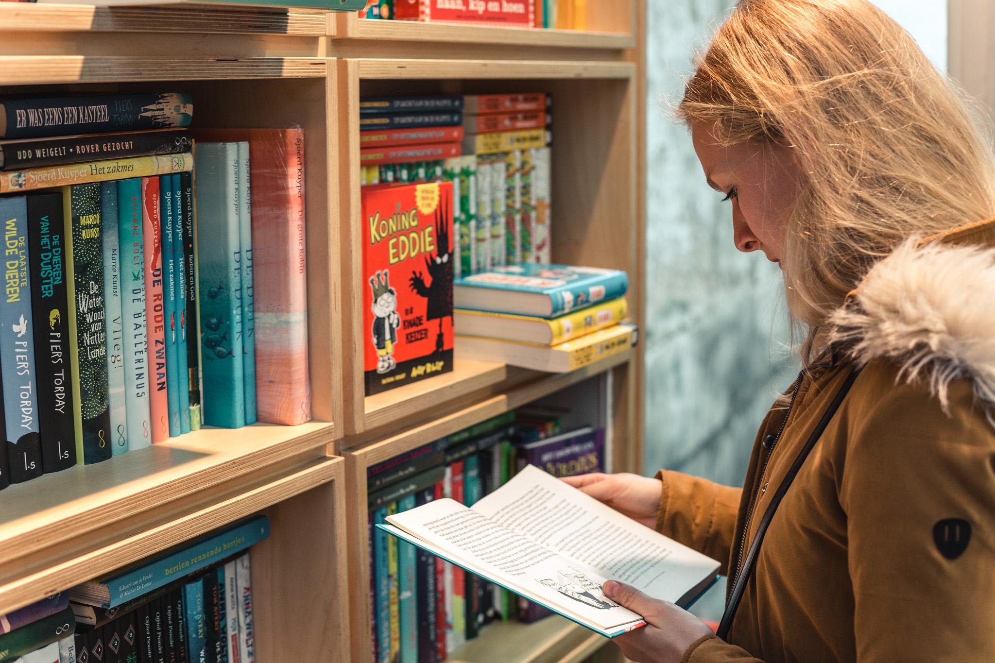 vrouw staat voor boekenkast en bladert door een boek