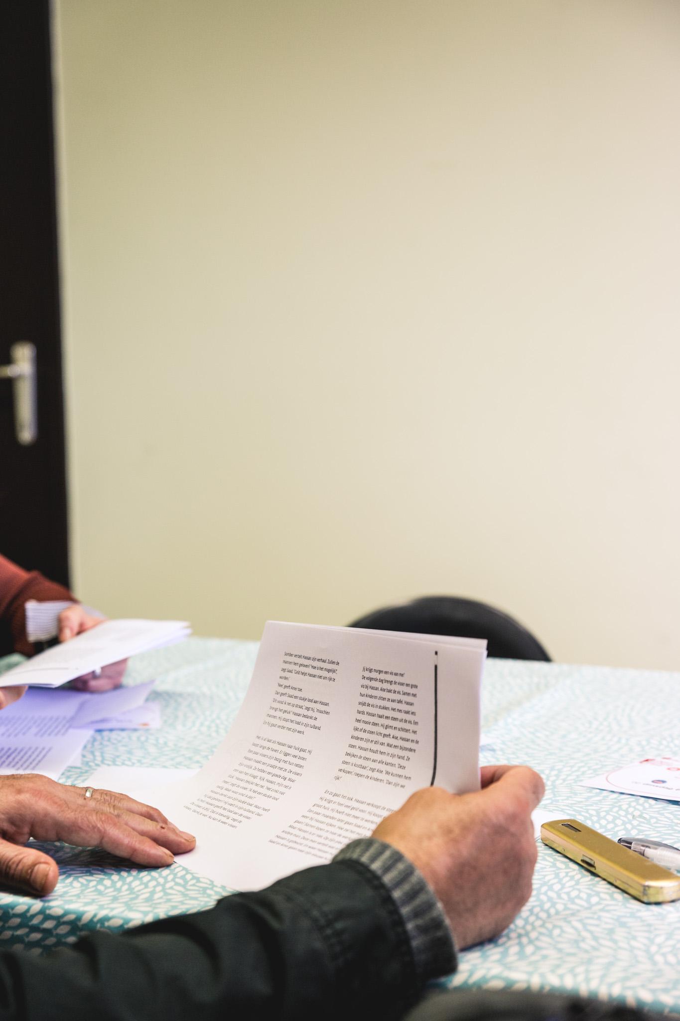persoon buiten beeld houdt blad met tekst in handen