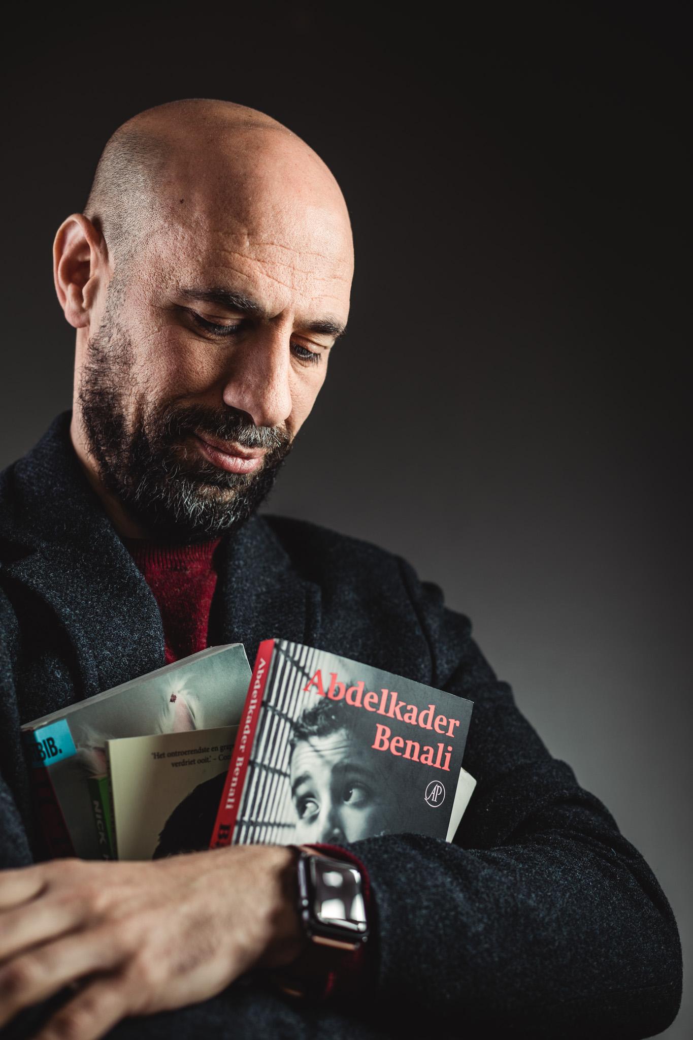 Portret van auteur Abdelkader Benali. Hij kijkt naar enkele van zijn geschreven boeken die hij in zijn armen houdt.