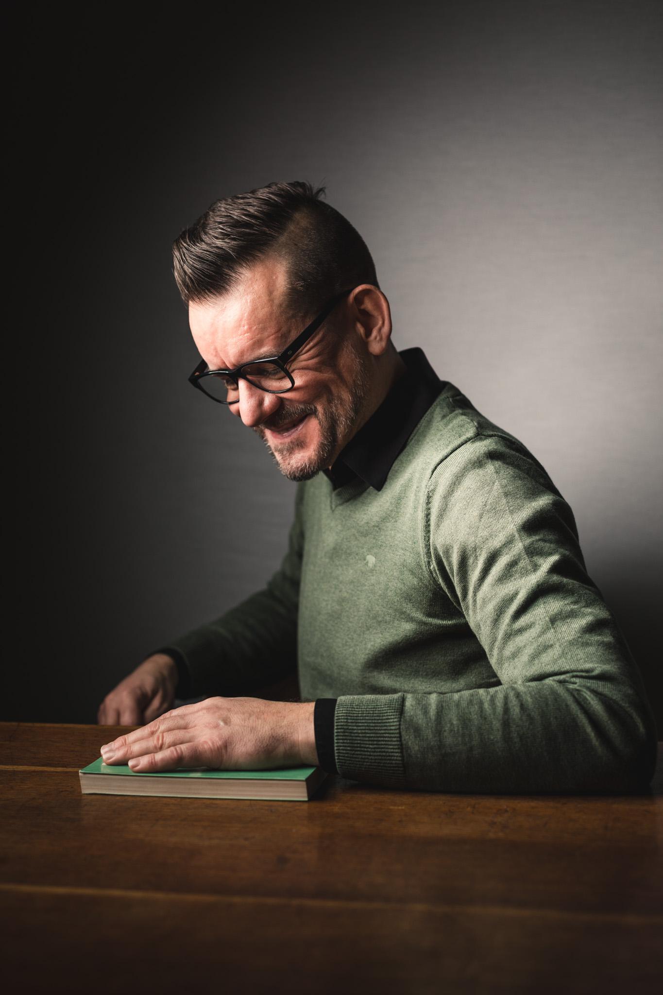 Jeugdauteur Bart Moeyaert zit lachend aan tafel. Voor hem ligt een boek op tafel, waarop zijn linkerhand rust.