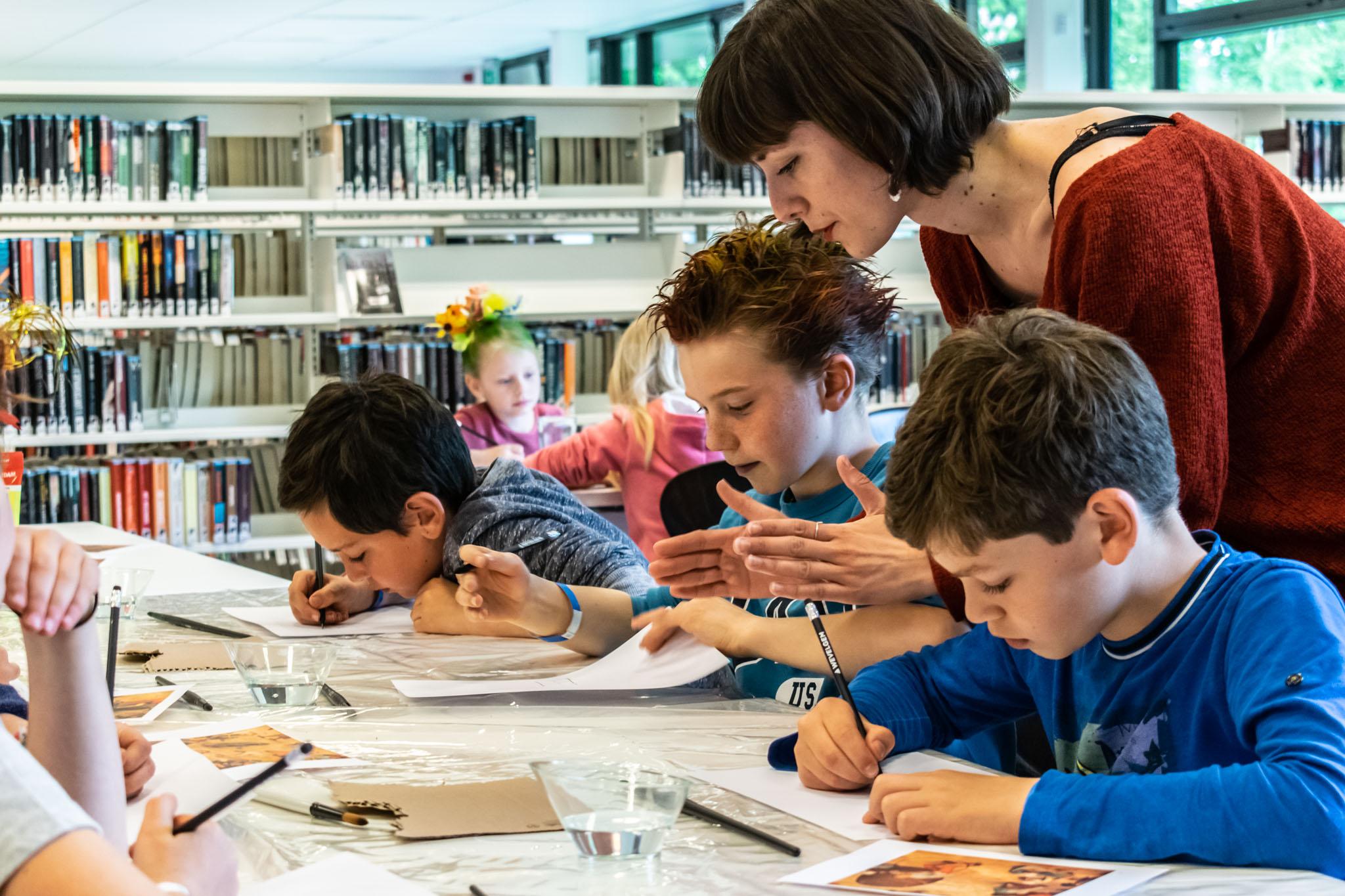 illustrator sassafras de bruyn geeft tips aan kinderen tijdens een tekenworkshop